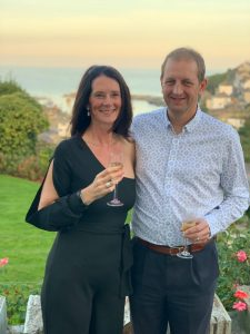 Photo of Marianne (Socially Maz) and George celebrating their 50th birthdays with a glass of champagne