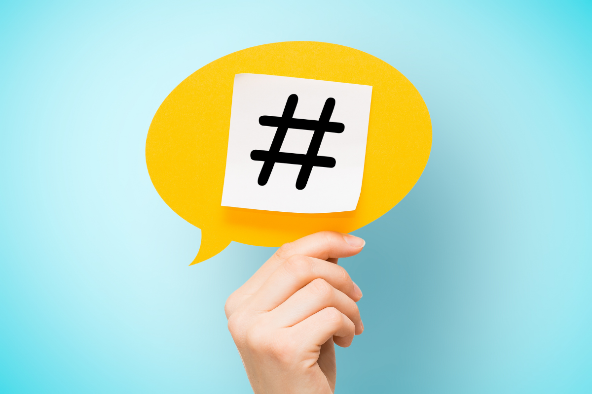 hashtag being held up by a hand on a yellow speech bubble